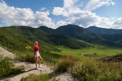 Ένα κορίτσι σε μια κόκκινη κορυφή και τα μπλε σορτς στην άκρη ενός απότομου βράχου στα βουνά Altai, είναι κατωτέρω πράσινοι τομεί στοκ φωτογραφίες