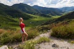 Ένα κορίτσι σε μια κόκκινη κορυφή και τα μπλε σορτς στην άκρη ενός απότομου βράχου στα βουνά Altai, είναι κατωτέρω πράσινοι τομεί στοκ εικόνα με δικαίωμα ελεύθερης χρήσης