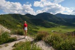 Ένα κορίτσι σε μια κόκκινη κορυφή και τα μπλε σορτς στην άκρη ενός απότομου βράχου στα βουνά Altai, είναι κατωτέρω πράσινοι τομεί στοκ εικόνα