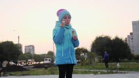 Ένα κορίτσι σε μια μπλε ζακέτα φυσά τις φυσαλίδες σαπουνιών το φθινόπωρο στην οδό building city evening high moscow rise απόθεμα βίντεο