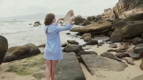 Ένα κορίτσι σε μια μπλε εσθήτα περπατά κατά μήκος της ακτής, βάζει σε ένα βιετναμέζικο καπέλο και χαμογελά απόθεμα βίντεο