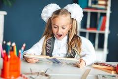 Ένα κορίτσι σε μια σχολική στολή εξετάζει ένα εγχειρίδιο με ένα έκπληκτο πρόσωπο κορίτσι που προσπαθεί να μελετήσει την κατοχή πά στοκ φωτογραφίες με δικαίωμα ελεύθερης χρήσης