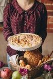 Ένα κορίτσι σε μια burgundy μπλούζα κρατά μια πίτα μήλων δίπλα σε ένα ψάθινο καλάθι με το ψωμί, το ρόδι και τις τουλίπες στοκ φωτογραφία με δικαίωμα ελεύθερης χρήσης