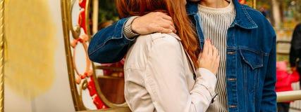 Ένα κορίτσι σε ένα μπεζ παλτό και ένας τύπος σε ένα σακάκι τζιν που αγκαλιάζει ανάμεσα σε ένα λούνα παρκ, ένας εύθυμος-πηγαίνω-κύ στοκ φωτογραφία