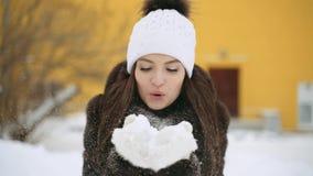 Ένα κορίτσι σε ένα παλτό βιζόν φυσά το χιόνι από τα γάντια της απόθεμα βίντεο