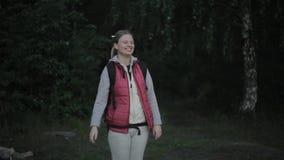 Ένα κορίτσι σε ένα πεζοπορώ στα ξύλα και τα γέλια φιλμ μικρού μήκους