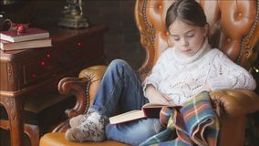 Ένα κορίτσι σε ένα πλεκτό άσπρο πουλόβερ διαβάζει την ιστορία απόθεμα βίντεο
