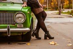 Ένα κορίτσι σε ένα σακάκι τζιν και μαύρες γυναικείες κάλτσες, pantyhose και μια μαύρη φούστα κλίνουν πέρα από το πράσινο αναδρομι στοκ φωτογραφία με δικαίωμα ελεύθερης χρήσης