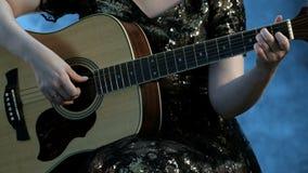 Ένα κορίτσι σε ένα φόρεμα βραδιού παίζει το α έξι-η ακουστική κιθάρα Οι δεξιές αφές οι σειρές, το αριστερό χέρι κρατούν τη χορδή φιλμ μικρού μήκους
