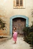 ένα κορίτσι σε ένα φόρεμα νεράιδων μιας πριγκήπισσας με μια κορώνα γυρίζει γύρω από το walkng στην πόρτα ενός αρχαίου σπιτιού κάσ Στοκ Φωτογραφίες