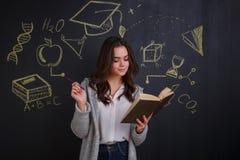 Ένα κορίτσι, στάσεις και με τα ineterses που διαβάζουν ένα βιβλίο, που στέκεται δίπλα στον πίνακα με μια εικόνα της επιστήμης Στοκ εικόνα με δικαίωμα ελεύθερης χρήσης