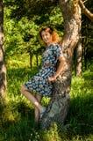 Ένα κορίτσι στέκεται κοντά σε ένα δέντρο στοκ εικόνα με δικαίωμα ελεύθερης χρήσης