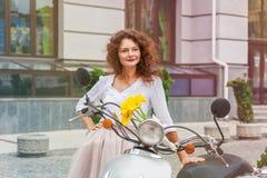Ένα κορίτσι στέκεται κοντά σε ένα μοτοποδήλατο στοκ εικόνα