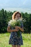 Ένα κορίτσι στέκεται με μια ανθοδέσμη των μαργαριτών Στοκ φωτογραφία με δικαίωμα ελεύθερης χρήσης