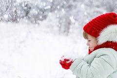Ένα κορίτσι στέκεται με μια πλευρά στο μέτωπο απολαμβάνοντας ειλικρινά έναν σωρό του χνουδωτού χιονιού στο χέρι της στοκ φωτογραφίες
