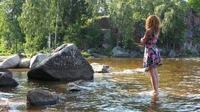 Ένα κορίτσι στέκεται χωρίς παπούτσια σε μια πέτρα στο νερό απόθεμα βίντεο