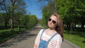 Ένα κορίτσι στα γυαλιά ηλίου περπατά στο πάρκο Το κορίτσι είναι έφηβος τζιν συνδυάζει Συγκινήσεις του κοριτσιού κίνηση αργή απόθεμα βίντεο