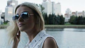 Ένα κορίτσι στα γυαλιά ηλίου που περπατά κοντά σε έναν ποταμό κίνηση αργή απόθεμα βίντεο