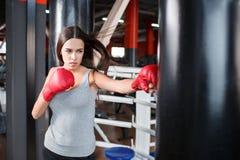 Ένα κορίτσι στα εγκιβωτίζοντας γάντια κτυπά μια punching τσάντα Στοκ Φωτογραφίες