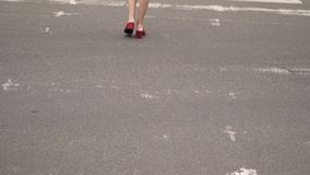 Ένα κορίτσι στα κόκκινα παπούτσια διασχίζει το δρόμο Ένας βηματισμός γυναικών ` s απόθεμα βίντεο
