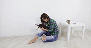 Ένα κορίτσι στα περιστασιακά ενδύματα κάθεται στο πάτωμα απόθεμα βίντεο
