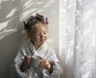 Ένα κορίτσι στα ρόλερ σε μια τήβεννο πίνει από μια κούπα κοντά στον τοίχο Στοκ φωτογραφίες με δικαίωμα ελεύθερης χρήσης
