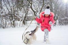 Ένα κορίτσι στα τρεξίματα ρόδινων σακακιών και καπέλων στο χιόνι δίπλα σε έναν γεροδεμένο Στοκ φωτογραφίες με δικαίωμα ελεύθερης χρήσης