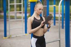 Ένα κορίτσι στην κατάρτιση εξετάζει την ταμπλέτα Στοκ Εικόνα
