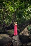 Ένα κορίτσι στη ζούγκλα στέκεται σε έναν βράχο Καταρράκτης στη ζούγκλα Στοκ Εικόνες