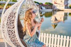 Ένα κορίτσι στις συνεδριάσεις θερινών φορεμάτων στον επάνω ανοικτό καφέ πεζουλιών Στοκ φωτογραφία με δικαίωμα ελεύθερης χρήσης