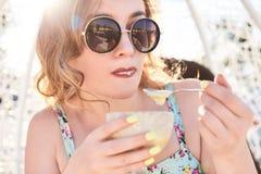 Ένα κορίτσι στο θερινό φόρεμα που τρώει τις σφαίρες ενός παγωτού σε ένα κύπελλο Στοκ εικόνα με δικαίωμα ελεύθερης χρήσης