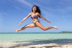 Ένα κορίτσι στο μπικίνι που πηδά στην παραλία θάλασσας Στοκ εικόνα με δικαίωμα ελεύθερης χρήσης