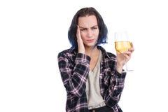 Ένα κορίτσι, συνοφρυώματα και κρατά το χέρι της στο κεφάλι της κρατά ένα ποτήρι του κρασιού Απομονωμένος στο λευκό στοκ φωτογραφίες με δικαίωμα ελεύθερης χρήσης