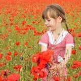Ένα κορίτσι συλλέγει τα λουλούδια παπαρουνών Στοκ Εικόνες