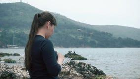 Ένα κορίτσι της ασιατικής εμφάνισης θαυμάζει μια όμορφη άποψη τοπίων και κρατά μια συσκευή στα χέρια της απόθεμα βίντεο