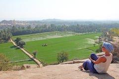 Ένα κορίτσι τουριστών κάθεται πάνω από το υποστήριγμα Hampi και εξετάζει τους πράσινους τομείς ρυζιού στοκ φωτογραφία με δικαίωμα ελεύθερης χρήσης
