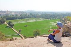 Ένα κορίτσι τουριστών κάθεται πάνω από το υποστήριγμα Hampi και εξετάζει τους πράσινους τομείς ρυζιού στοκ φωτογραφίες