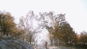 Ένα κορίτσι τρέχει και πηδά στα όπλα του φίλου της στο λόφο μια παγωμένη ημέρα πρωινού απόθεμα βίντεο