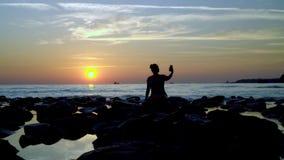 Ένα κορίτσι φωτογραφίστηκε στο τηλέφωνο στο υπόβαθρο του ηλιοβασιλέματος απόθεμα βίντεο
