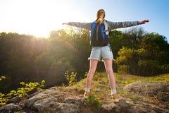 Ένα κορίτσι backpacker απολαμβάνει τη θέα στην ανατολή ή το ηλιοβασίλεμα στο ελαφρύ κτύπημα Στοκ Εικόνες