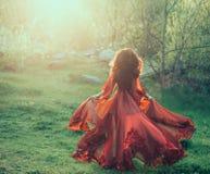 Ένα κορίτσι brunette με τα κυματιστά, παχιά τρεξίματα τρίχας στη συνεδρίαση του ήλιου Φωτογραφία από την πλάτη, χωρίς ένα πρόσωπο Στοκ φωτογραφίες με δικαίωμα ελεύθερης χρήσης