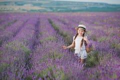 Ένα κορίτσι Brunette σε ένα καπέλο αχύρου που κρατά ένα καλάθι με lavender Ένα κορίτσι Brunette με δύο πλεξούδες σε έναν lavender Στοκ εικόνα με δικαίωμα ελεύθερης χρήσης