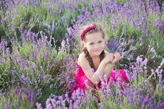 Ένα κορίτσι Brunette σε ένα καπέλο αχύρου που κρατά ένα καλάθι με lavender Ένα κορίτσι Brunette με δύο πλεξούδες σε έναν lavender Στοκ φωτογραφία με δικαίωμα ελεύθερης χρήσης