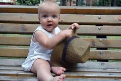 Ένα κοριτσάκι με μια μεγάλη συνεδρίαση καπέλων στον πάγκο Στοκ εικόνα με δικαίωμα ελεύθερης χρήσης