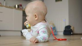 Ένα κοριτσάκι σε ένα romper κοστούμι που βρίσκεται στο πάτωμα φιλμ μικρού μήκους