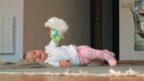 Ένα κοριτσάκι στα ρόδινα καλσόν που βρίσκονται σε ένα πάτωμα με τα πρόβατα παιχνιδιών απόθεμα βίντεο