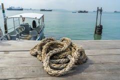 Ένα κουλουριασμένο σχοινί στην ξύλινη αποβάθρα, η θάλασσα και η βάρκα είναι υπόβαθρο στοκ φωτογραφία