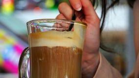 Ένα κουταλάκι του γλυκού αφαιρεί τον αφρό από τα glas καφέ σε ένα γυαλί του ayrish φιλμ μικρού μήκους