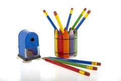 Κολάζ των μολυβιών σε ένα φλυτζάνι με μια μπλε ξύστρα για μολύβια Στοκ Εικόνες