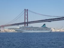 Ένα κρουαζιερόπλοιο πλέει κάτω από τη γέφυρα της 25ης Απριλίου στη Λισσαβώνα, Πορτογαλία, Ευρώπη στοκ εικόνα
